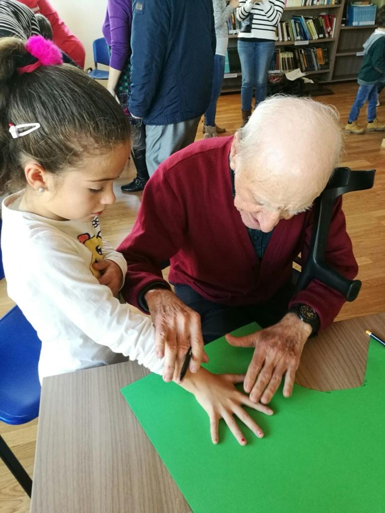 """Una niña y un residente de la residencia de mayores de Felechosa participando de una actividad junto dentro del programa intergeneracional """"Vivencias"""". Están dibujando sus manos."""