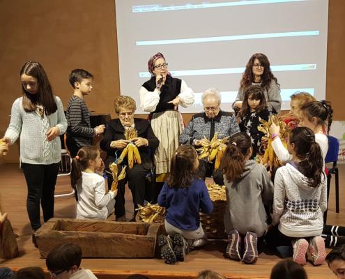 """Varios niños y ancianos participan de una actividad de oficios tradicionales dentro del programa de convivencia intergeneracional """"Vivencias"""". Con la temática del campo, tienen en sus manos unas mazorcas de maíz."""