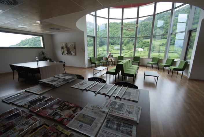 Mujer leyendo una revista en la Biblioteca de la Residencia Spa de Felechosa. Sobre la mesa hay muchos periódicos y revistas.