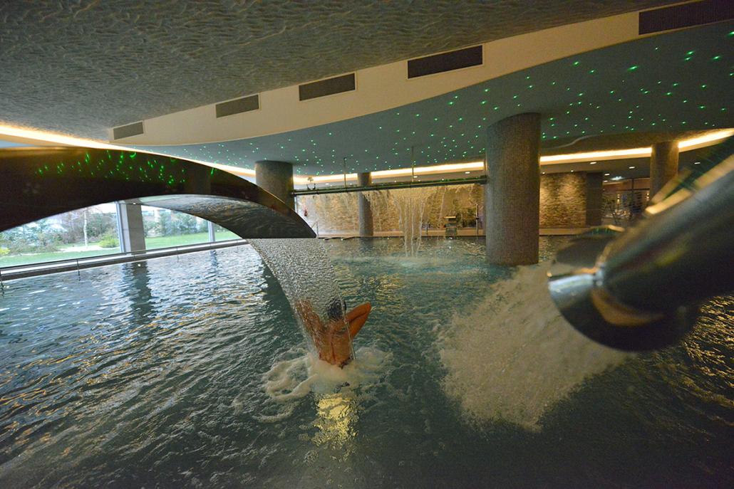 Mujer disfrutando de los chorros de espalda de la piscina dinámica del spa de la Residencia Spa de Felechosa