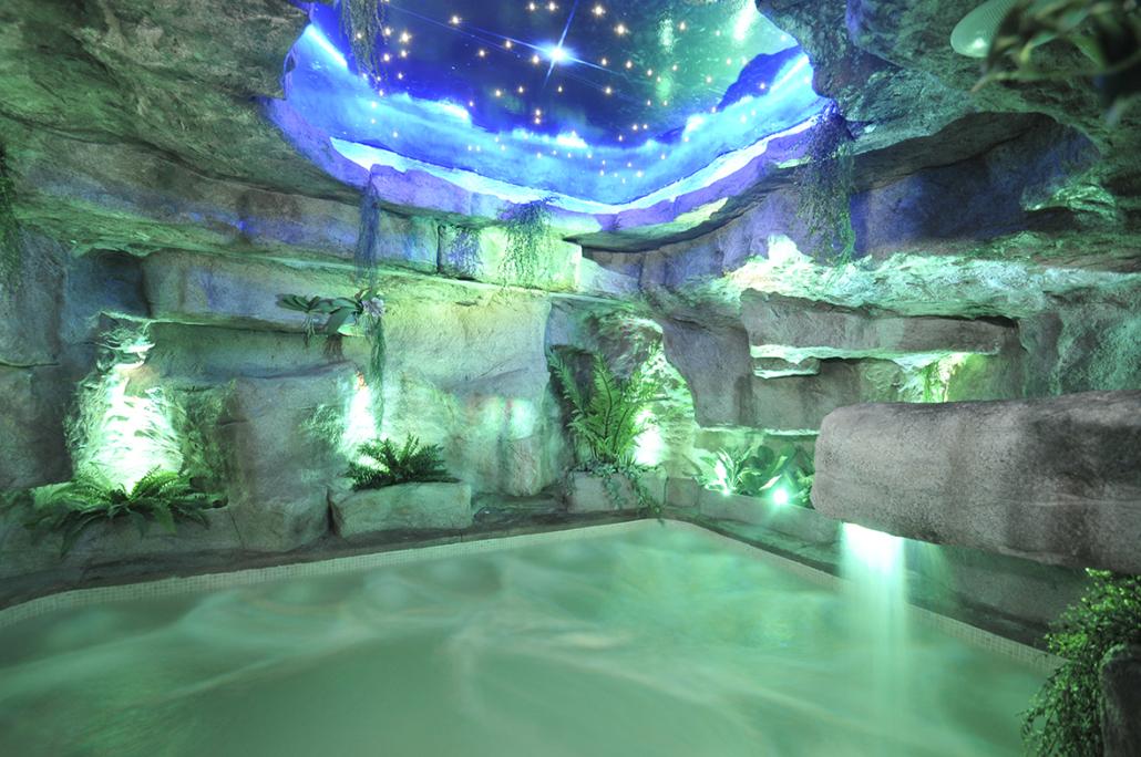 Jacuzzi iluminado en tonos verdes y azules del spa de la Residencia Spa de Felechosa